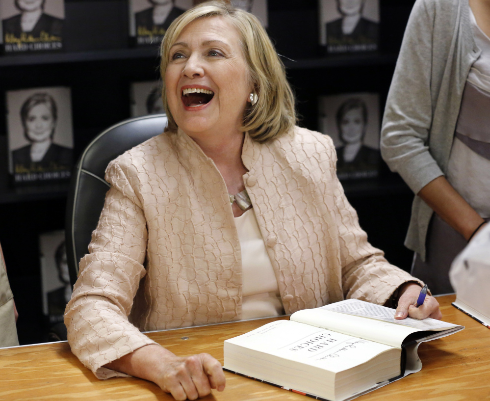 "Former Secretary of State Hillary Rodham Clinton laughs while speaking with a customer at a signing for her book ""Hard Choices,"" at Bunch of Grapes Bookstore, Wednesday in Vineyard Haven, Mass."