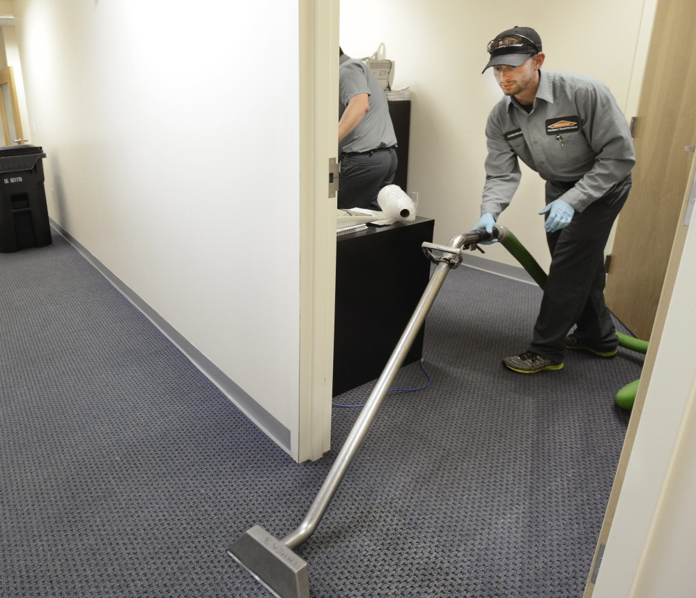 Christopher Steckino of Servpro cleans flooded offices on Main Street in South Portland on Thursday.