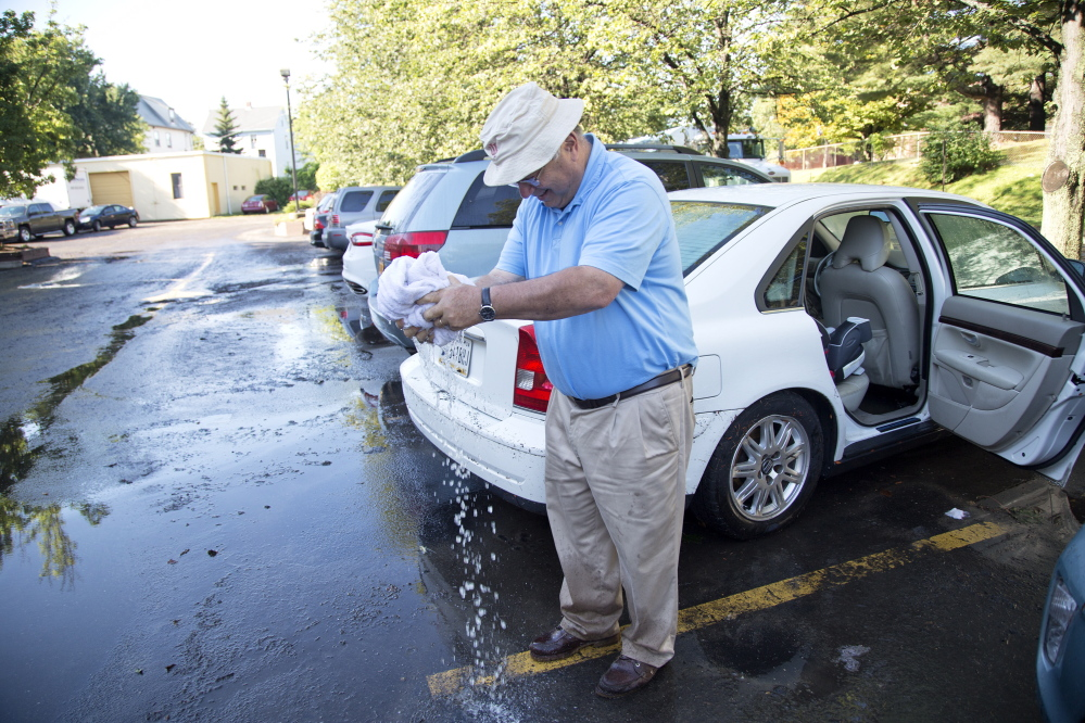 Martin Spechler of Bloomington, Ind., wrings out a towel as he sops up water from the back seat of his car Thursday. His vehicle was among dozens damaged by flooding at the La Quinta Inns & Suites in Portland.