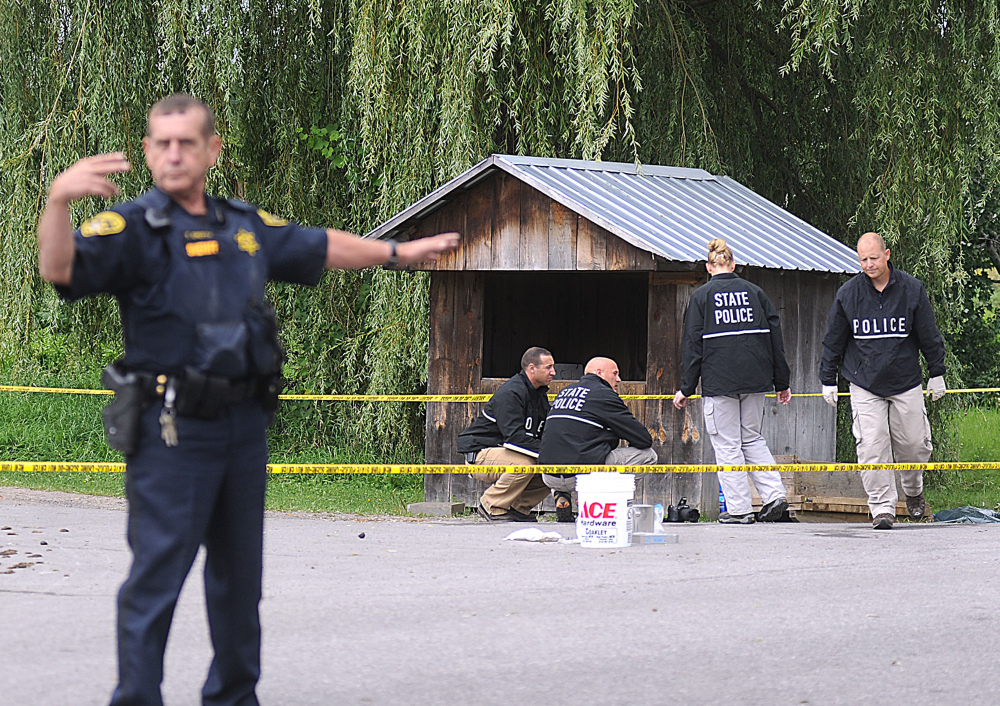 New York State Police crime scene investigators search for clues at a roadside vegetable stand in Oswegatchie, N.Y., on Thursday as they investigate the abduction of two Amish sisters.