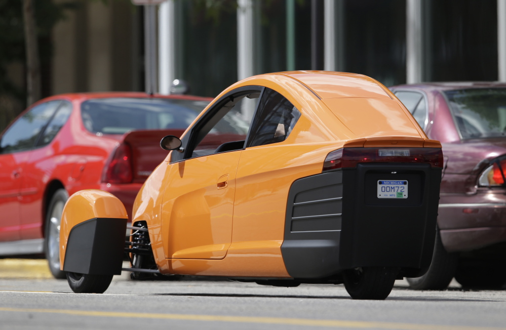 The Elio, a three-wheeled prototype vehicle, is shown in traffic in Royal Oak, Mich.