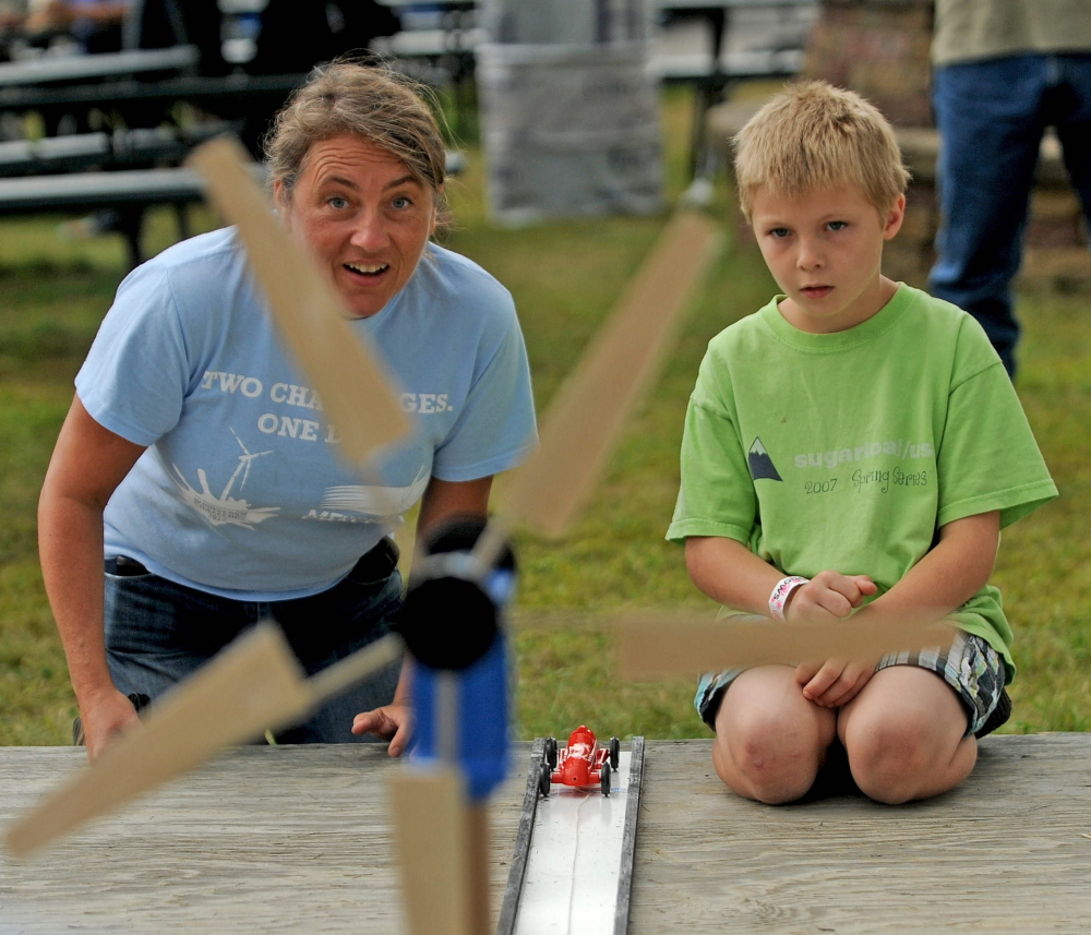 Tanner Mayo, 9, of Temple learns about wind power Friday from Lisa Twombly with the build-your-own-wind-blade challenge at the Skowhegan State Fair