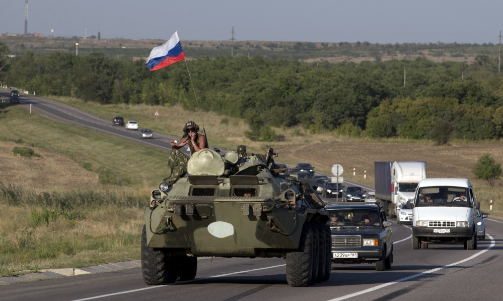 A Russian military vehicle maneuvers on a road behind a convoy of aid trucks, 9 miles from the Ukrainian border in the Rostov-on-Don region, Russia, on Friday. The Ukraine president says his forces engaged with Russian vehicles in Ukraine.