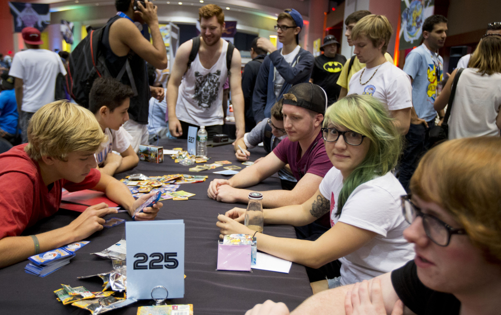 Competitors, from left, Henry Ross-Clunis, Kyle Sabelhaus, Nicholena Moon, and Jimmy Pendarvis, trade cards and discuss strategy for the last chance qualifier in the Pokemon trading card game for the 2014 Pokemon World Championships in Washington on Friday.
