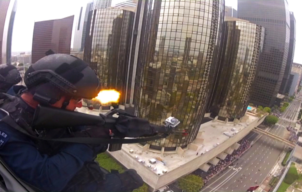 Police officers fire blank rounds from a helicopter in a drill simulating a terrorist attack in downtown Los Angeles. After a decade of sending military equipment to civilian police departments, Washington is reconsidering the idea in light of the violence in Ferguson, Mo.