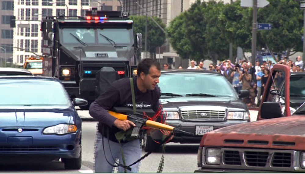 In this July 6, 2013, still frame from a video produced by the Los Angeles Police Department, a man posing as a terrorist runs as a heavily-armored vehicle approaches in a drill simulating a terrorist attack in downtown Los Angeles. The Associated Press