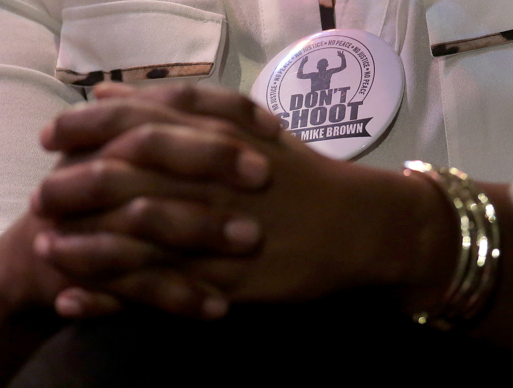 Michael Brown's mother,  Lesley McSpadden, wears a don't shoot button during a rally at Greater Grace Church, Sunday, for their son who was killed by police last Saturday in Ferguson, Mo.