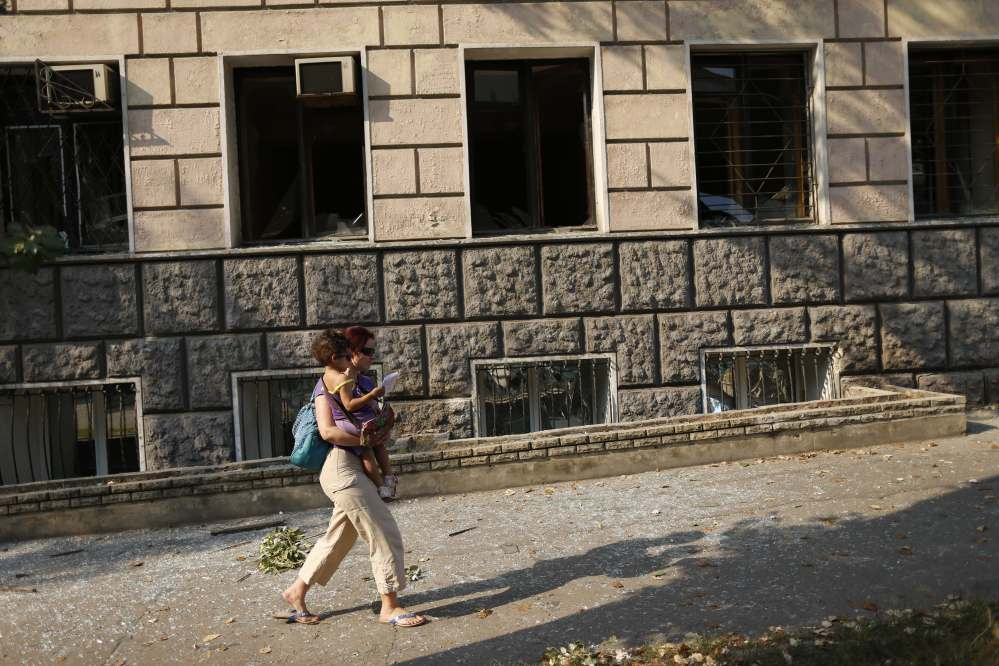 A woman with a child walks past an apartment building damaged by shelling in the center of Donetsk, eastern Ukraine, Thursday, Aug. 14, 2014. Ukrainian forces stepped up efforts to dislodge the separatists from their last strongholds in Donetsk and Luhansk, with more heavy shelling overnight.