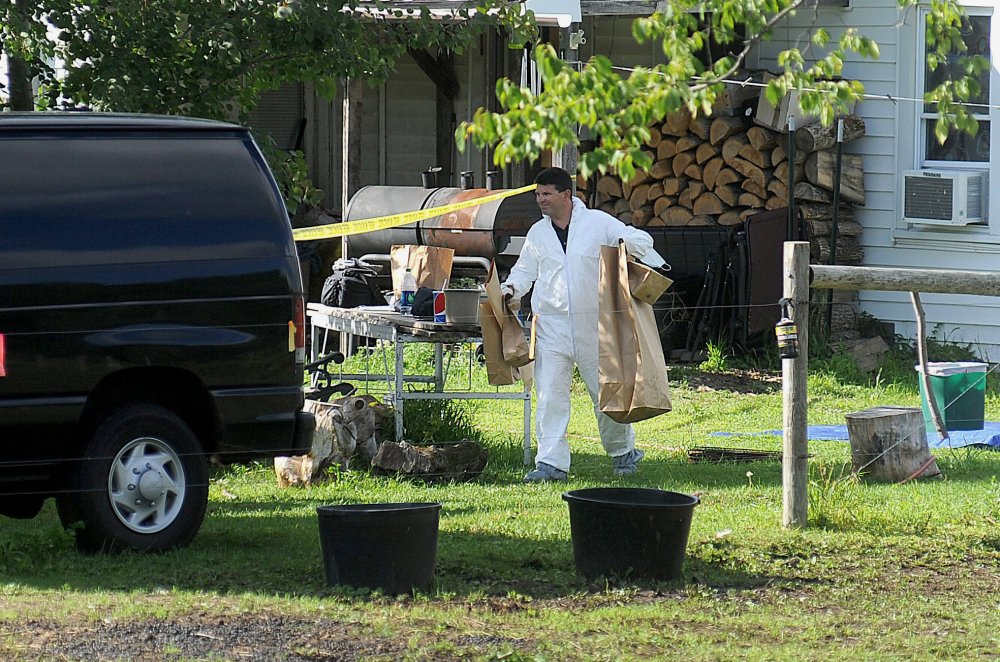 A New York State Police crime scene investigator carries evidence to a van Sunday at the home of suspected kidnappers Stephen Howells Jr. and Nicole Vaisey, in Hermon, N.Y. The father of two Amish girls abducted in northern New York last week says he feels sorry for the two people authorities say kidnapped and sexually abused his daughters.