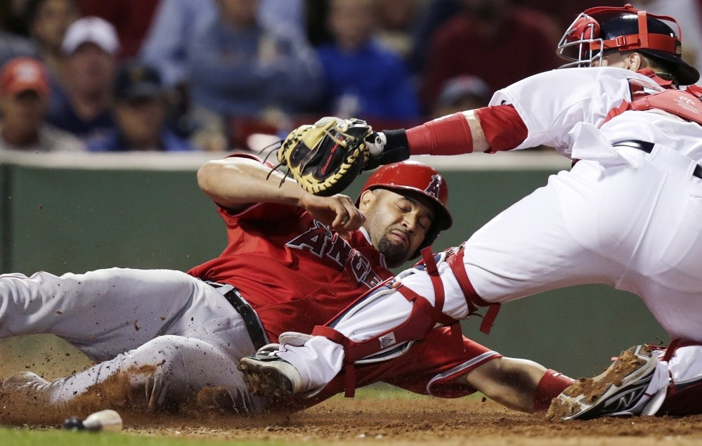 Los Angeles Angels' Albert Pujols is tagged out at home by Red Sox catcher Christian Vazquez during the eighth inning at Fenway Park in Boston on Monday. Pujols was originally called safe, but the call was overturned by video replay review. The Associated Press