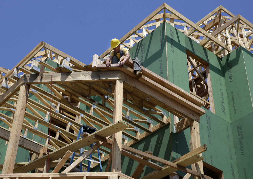 In this July 30 photograph, a builder works on the construction of new homes in Belmar, N.J.
