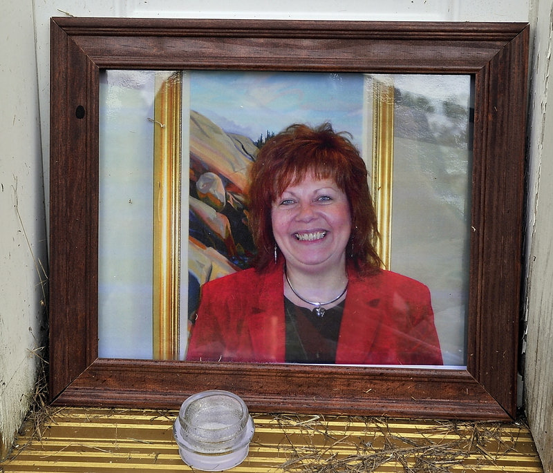 A memorial shows a photo of Lynn Arsenault, 55, who was killed in Belfast in 2013.