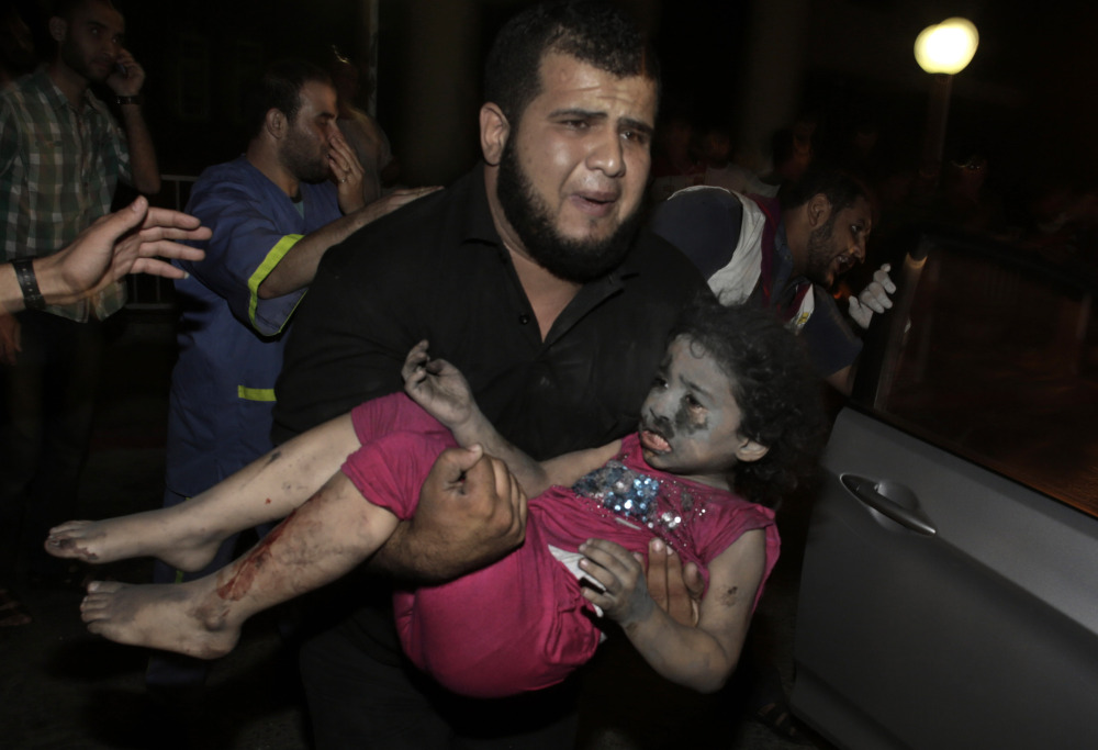 A Palestinian man carries an injured girl into the Shifa hospital after Israeli strikes that hit Gaza City on Tuesday.