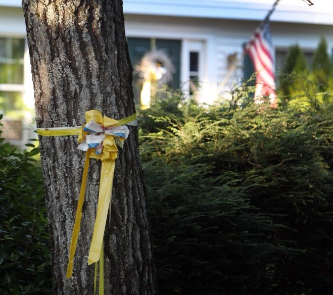 A ribbon is tied to a tree outside the home of American freelance journalist James Foley on Tuesday in Rochester, N.H. Islamic State militants released a video Tuesday that purports to show the killing of Foley.