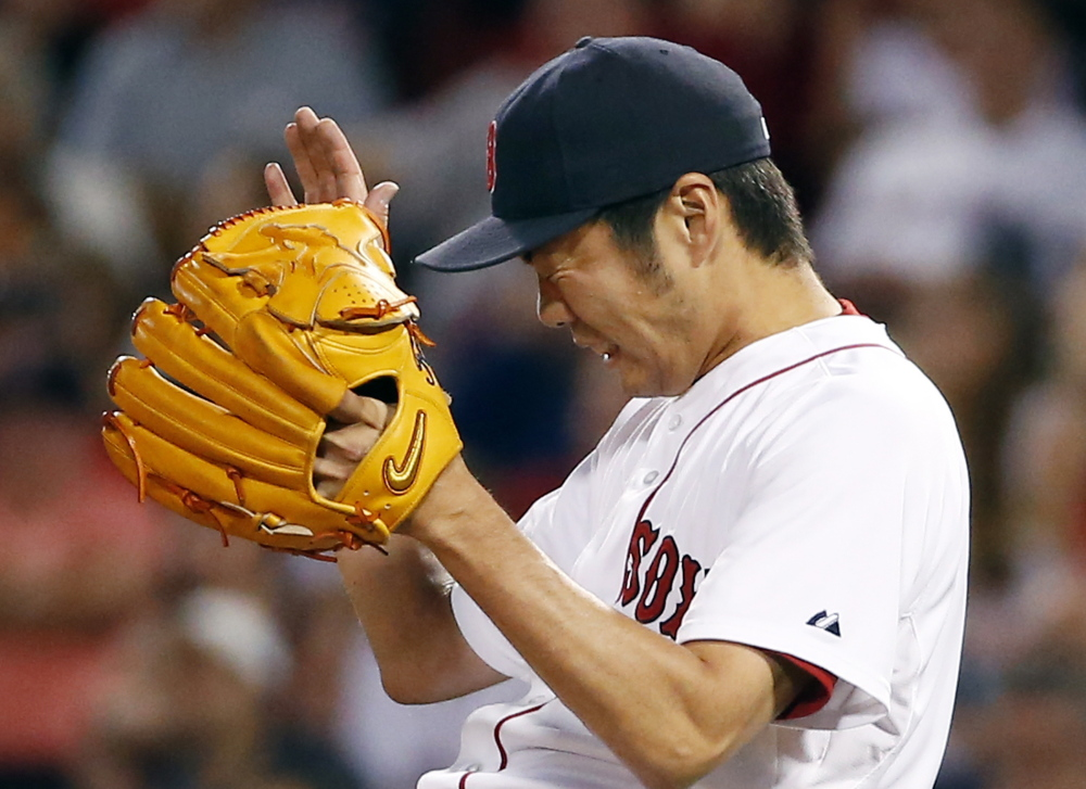 Red Sox relief pitcher Koji Uehara grimaces as he gives up a tie-breaking RBI double to the Los Angeles Angels' Chris Iannetta in the ninth inning Tuesday night at Fenway Park.