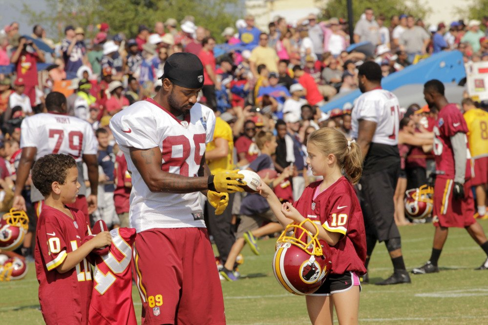 Santana Moss (89) of Washington's NFL team signs autographs with Kaya Todd, 9, right, and Devin Wright, 7, after a joint practice with the New England Patriots in Richmond, Va. In the time-warped world of professional sports, anything past 30 opens conversations about players being past their prime. If you get to 35, well, then the geriatric jokes start flying.