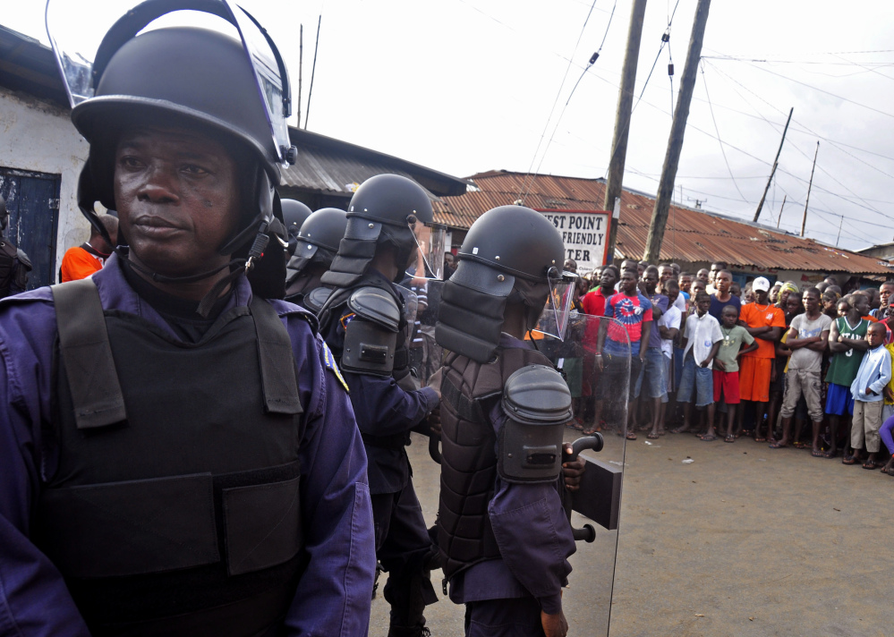 Liberian security forces control a crowd Wednesday in Monrovia's West Point slum as the government clamps down on the movement of people to stop the spread of Ebola.