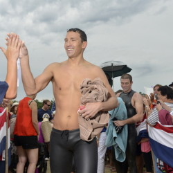 Mike, an active-duty Navy SEAL, high-fives the crowd Thursday after coming ashore on Sebago Lake in Standish after his fundraising swim.