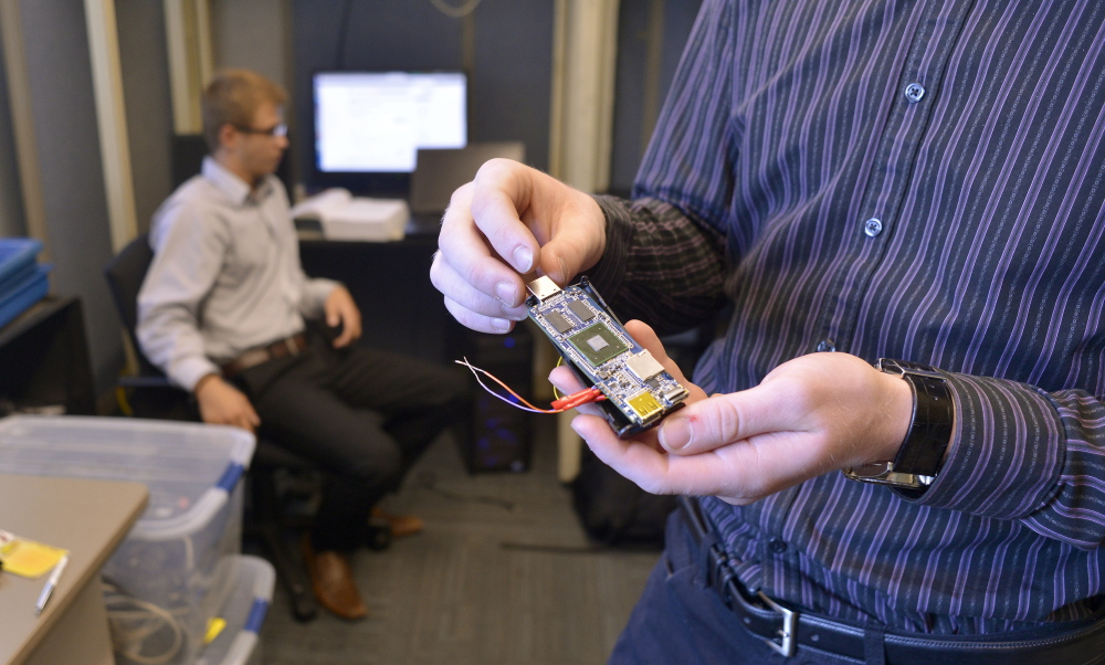 Michael Guesev, left, works at USM's new Cyber Security Lab at the Portland campus on Wednesday as Samuel Barton shows a micro computer used for data monitoring.