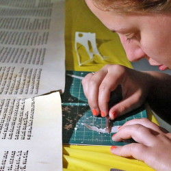 "Rachel Salston of Los Angeles, who is a ""soferet,"" one of the country's few female scribes, repairs a damaged Torah used by the Jewish Academy of Orlando in Maitland, Fla."
