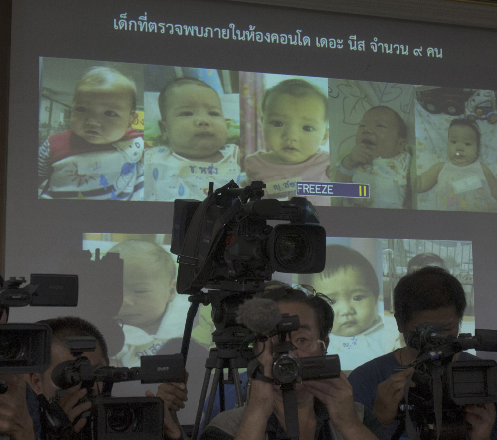 Pictures of babies fathered by a Japanese man who is at the center of a surrogacy scandal are displayed at police headquarters in Chonburi, Thailand.