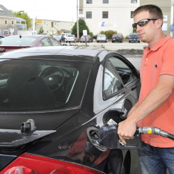 Kerry Dineen fills his 2001 Mercury Cougar at the Irving station on Commercial Street.