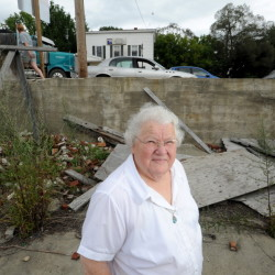 Alice Emery stands in the foundations of two burned out buildings on Main Street in Norridgewock on Friday. Emery was housekeeper for Harold Alfond for 45 years and has taken on the mission to turn the eyesores in to green space for the community.