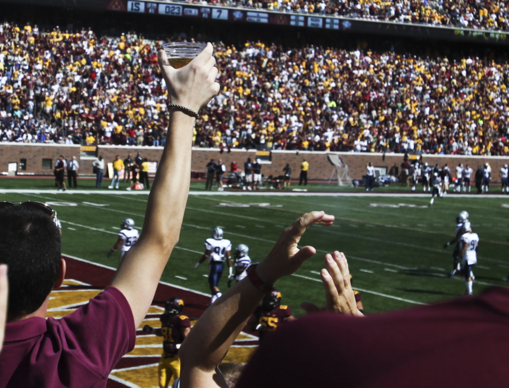 A football fan hoists a beer during a college game between Minnesota and New Hampshire at TCF Bank Stadium in Minneapolis, Minn., in September 2012. A growing number of revenue-starved schools are bringing the party inside, opening taps in concourses that traditionally have been alcohol-free zones.
