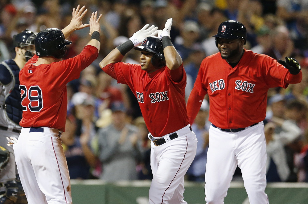 Red Sox outfielder Yoenis Cespedes, center, celebrates his home run, which also drove in Daniel Nava (29) and David Ortiz, right, in the sixth inning against the Seattle Mariners in Boston on Friday.