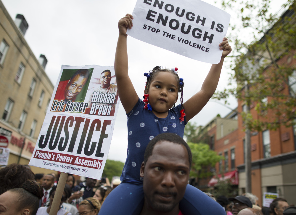 Ameariah Shearin holds a sign atop her father Theodore during a Saturday march through Staten Island.