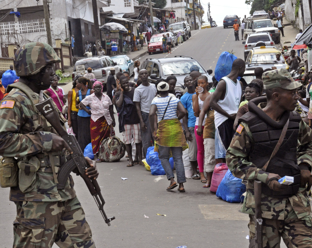 Liberian soldiers look for signs of the Ebola virus in the West Point area of Monrovia on Saturday. Sierra Leone's new law imposes prison terms for hiding Ebola patients.