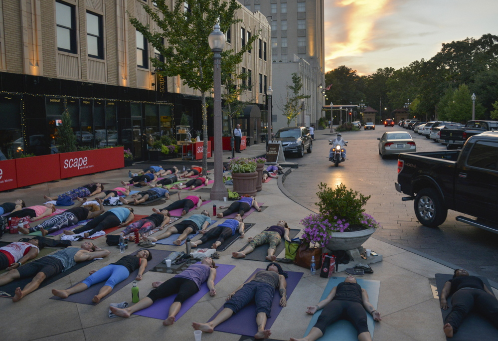 Yoga enthusiasts enjoy a free class at St. Louis' Maryland Plaza, several blocks south of Delmar Boulevard – the de facto dividing line between the city's wealthier, majority-white area to the south and the majority-black area north of the east-west boulevard.