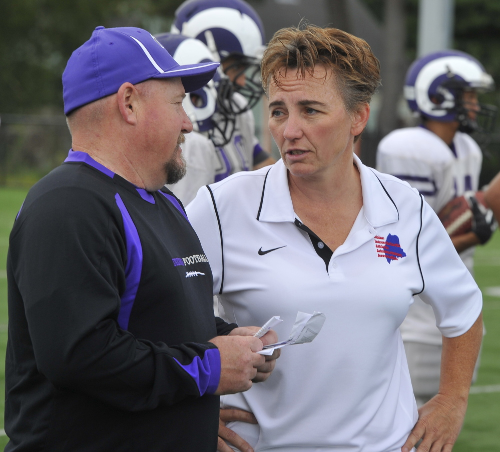 Mel Craig, right, the Deering High athletic director talking with football coach Matt Riddell, said parents often become involved in their child's sports when a problem arises, and it's best to meet parents in person to resolve conflicts.