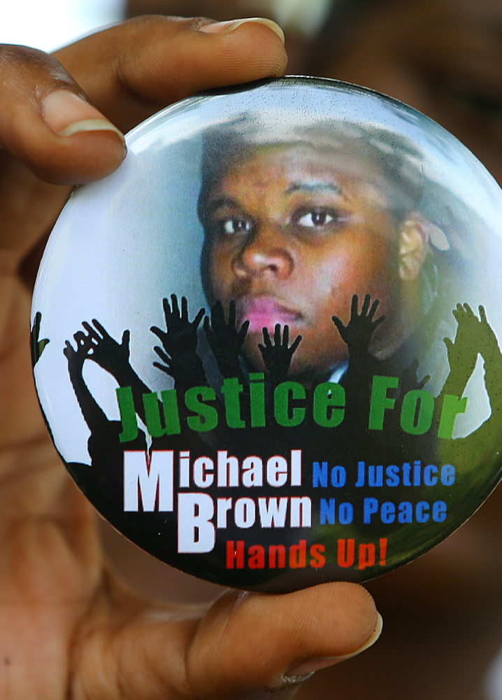 Michael Brown Jr., who was fatally shot by a police officer in Ferguson, Mo., is shown in a photo on a button.