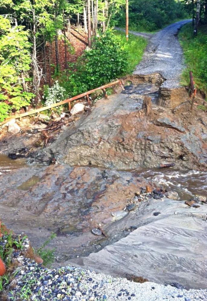 An overflowing stream caused by a record rainfall damaged this access road to two properties in Freeport. The photo was taken before temporary repairs were made.