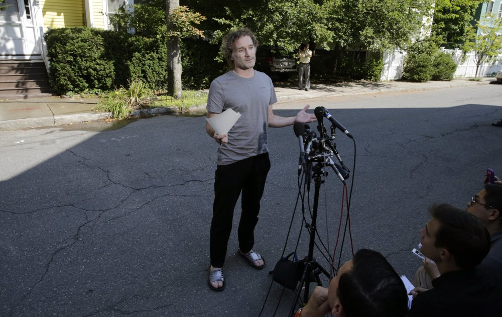 Peter Theo Curtis reads a statement to reporters outside his mother's home in Cambridge, Mass., Wednesday.