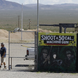 A man closes off an entrance to the Last Stop outdoor shooting range Wednesday in White Hills, Ariz. Gun range instructor Charles Vacca was accidentally killed