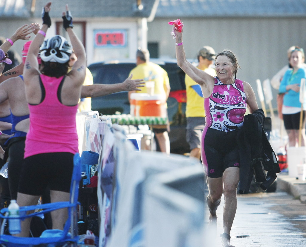 Marcia Feller of Yarmouth waves to a SheJams teammate as she enters the transition area after finishing the swimming portion at the Rev3 Triathlon on Sunday in Old Orchard Beach. The SheJams race was an Olympic distance triathlon featuring only female competitors. Photos by Jill Brady/Staff Photographer