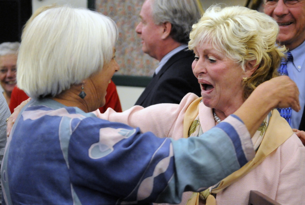 Gilda Nardone, executive director of Women, Work and Community, left, hugs University of Maine at Augusta president  Allyson Handley after the announcement of the plan to change the name of the Gannett Building on Water Street in Augusta to Handley Hall.