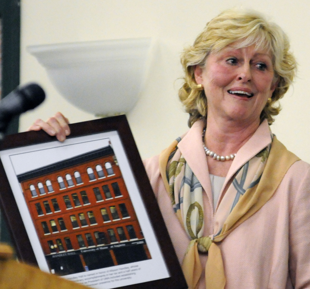 University of Maine at Augusta President Allyson Handley holds up a framed photo after she found out Friday the school as renaming one of its buildings for her.