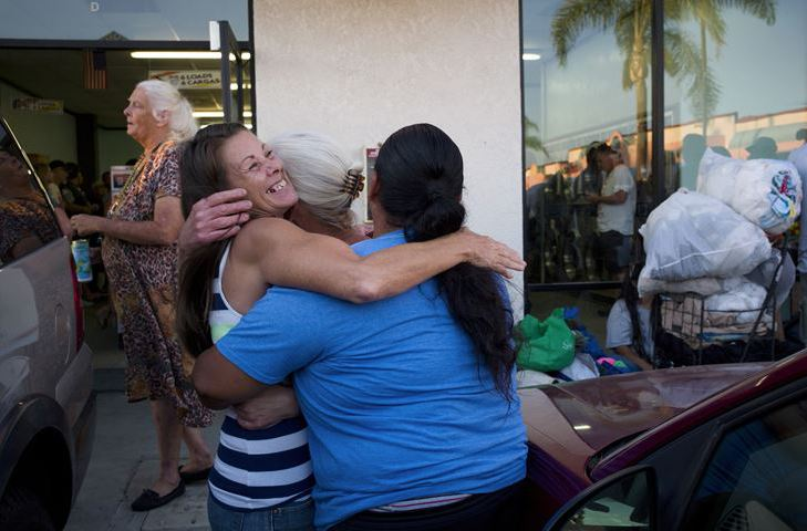 Jeanne Strickler, left, who is homeless, hugs her friends outside a laundromat before a Laundry Love event Aug. 13 in Huntington Beach, Calif.