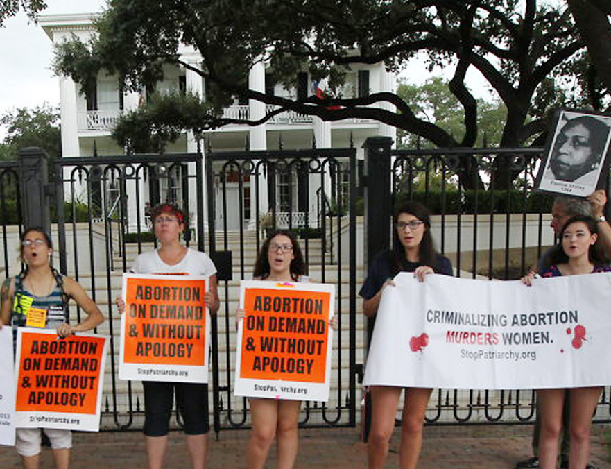 Abortion rights supporters take a stand outside the Texas governor's mansion on Friday after a federal judge in Austin struck down two provisions of the 2013 Texas law that restricts abortions.