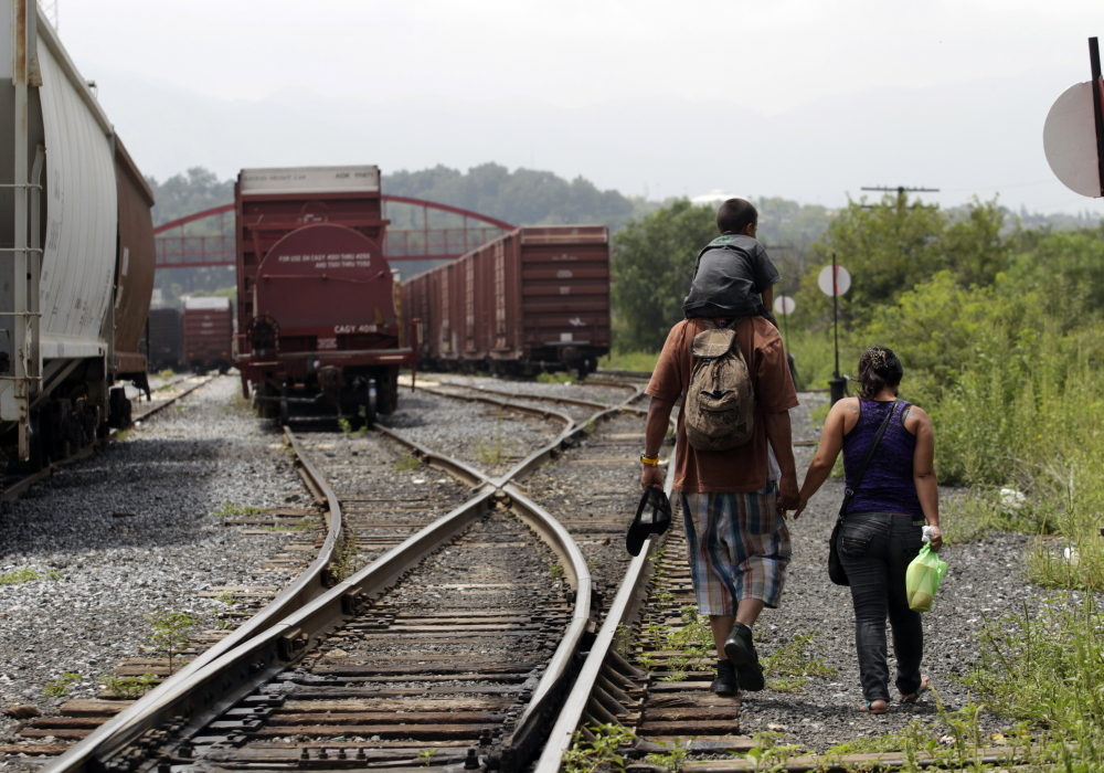 "A couple from El Salvador walk with their 3-year-old son on the train tracks in Saltillo early this month. The young family planned to catch the cargo train nicknamed ""The Beast"" to the United States."