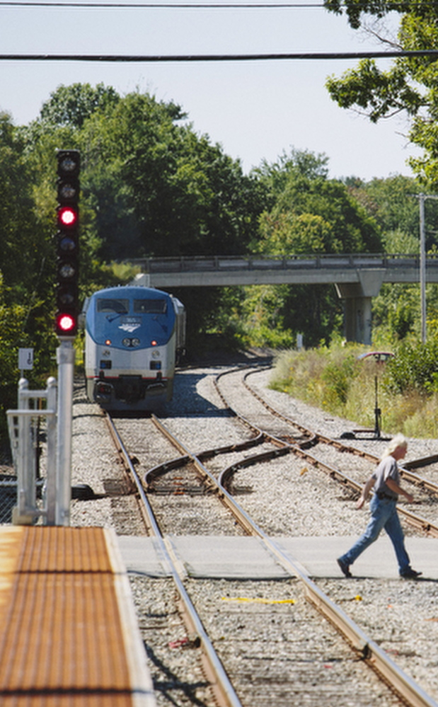 Brunswick resident William Capistran crosses the tracks near the Brunswick train station Friday. Residents of a neighborhood have complained about the potential impacts of an Amtrak layover facility.
