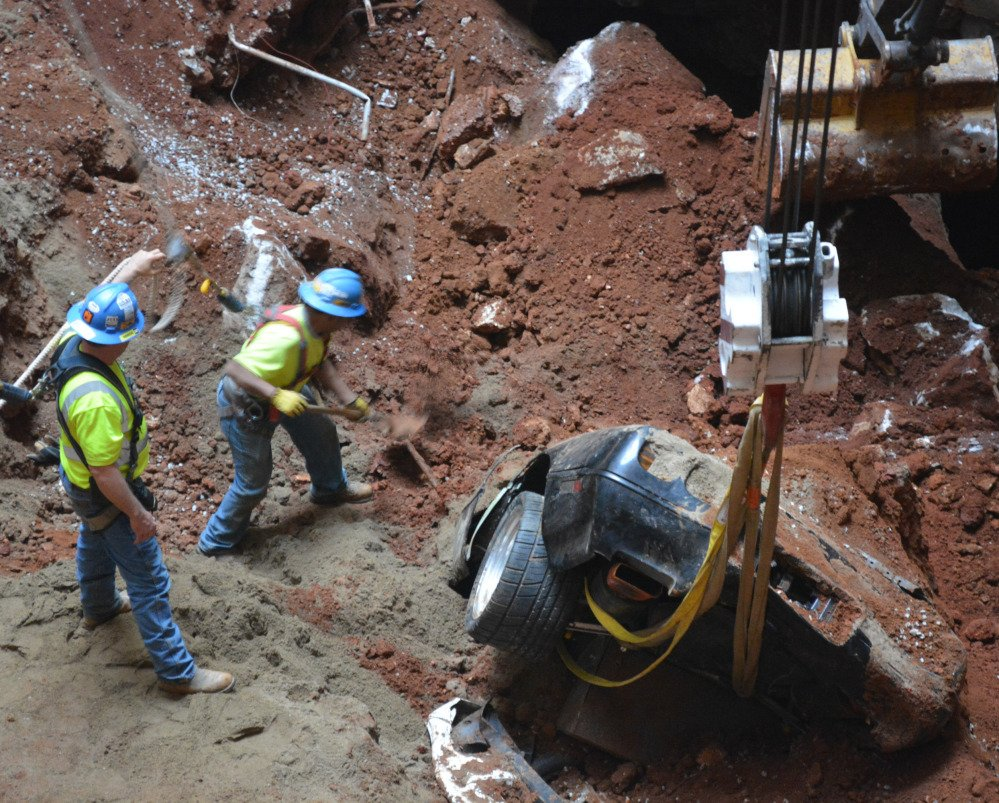 Workers pull a car from a massive sinkhole that opened up in the Skydome at the National Corvette Museum in Bowling Green, Ky., last February. Museum officials say safety work needed to retain the popular hole would cost $1 million.