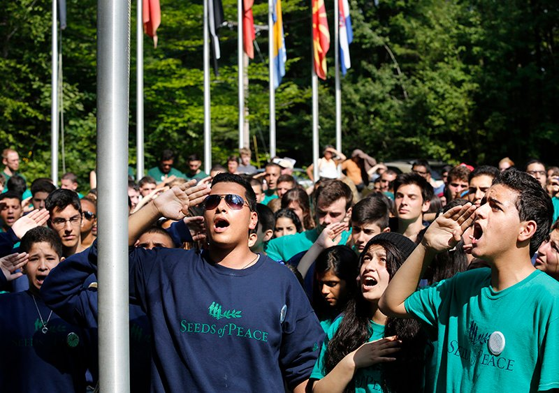 "Abed-Al-Raheem, center, leads fellow Palestinian campers in singing the national anthem ""Fida'i"" as the Palestinian flag is raised during opening ceremonies at Seeds of Peace. Derek Davis/Staff Photographer"