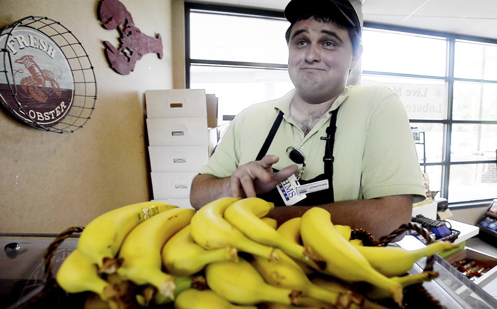 "Jonathan Niederer of Biddeford sells bananas – with a song – at the Kennebunk service plaza on the southbound side of the Maine Turnpike. His pitch-perfect selling has earned him the praise of his managers and sales bonuses. ""Once I started doing it, I just noticed I got a lot more business, I'd say two to three times more business,"" he said. ""And it's because I sing."" Shawn Patrick Ouellette/Staff Photographer"