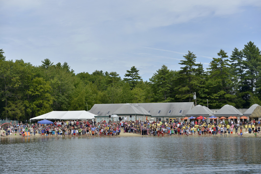A crowd gathers on the beach to welcome the Navy SEALs after their 13.5-mile swim in Sebago Lake to raise money for Camp Sunshine on Thursday.