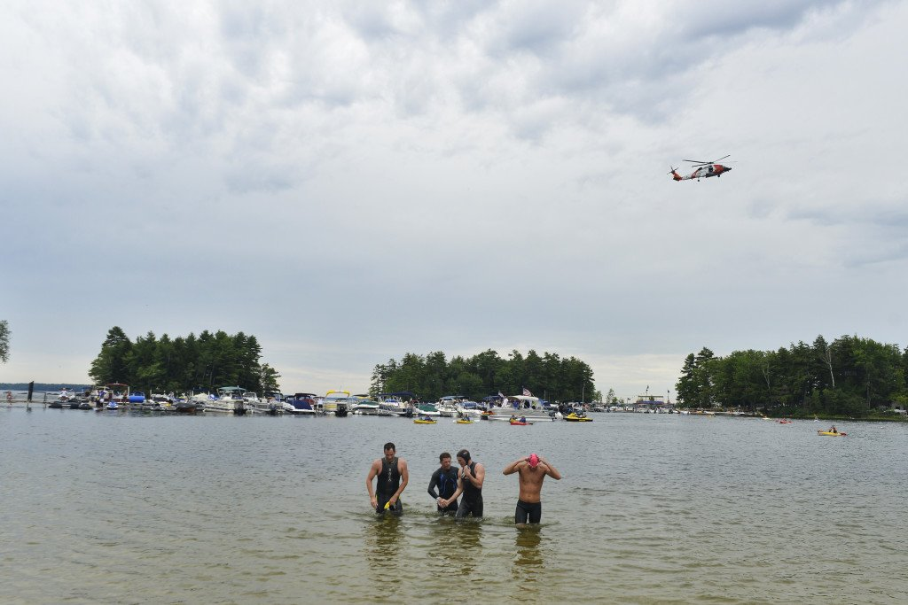 A United States Coast Guard helicopter flies overhead as active-duty Navy SEALs, from left, Mike, Lew, Matt and Chad, arrive on the shore of Sebago Lake after a 13-mile swim to raise money for Camp Sunshine on Thursday. Only their first names were given because of their active-duty status.
