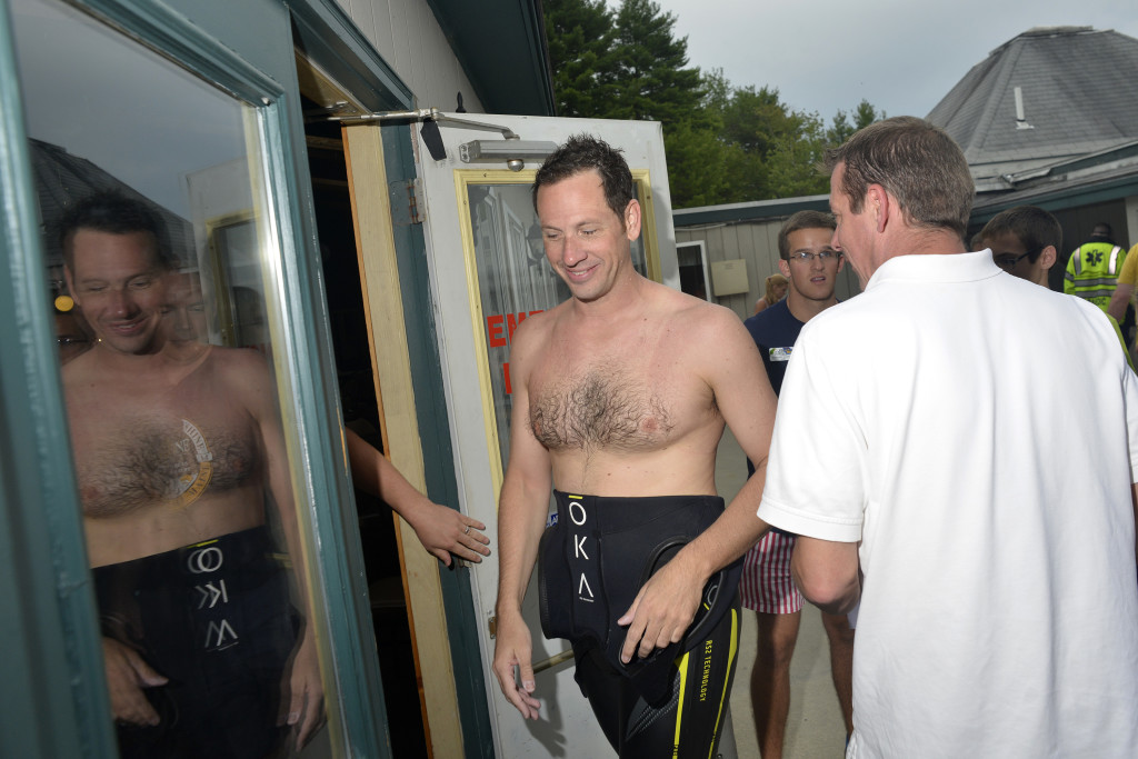Active-duty Navy SEAL and the Camp Sunshine fundraiser organizer Mike is ushered into a changing room after arriving on the shore of Sebago Lake following a 13-mile swim to raise money for Camp Sunshine in Casco on Thursday.